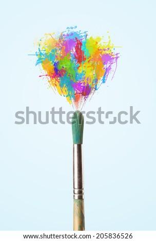 Paintbrush close-up with colored paint splashes - stock photo