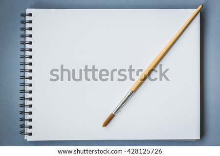 Paintbrush on blank drawing paper book with vintage tone