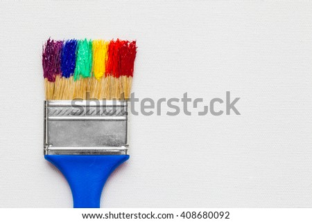 Paintbrush with paint on white artist canvas - stock photo