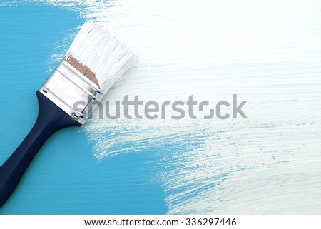 Paintbrush with white paint painting over light blue colour on a pine board - stock photo