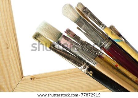 Paintbrushes against a white background with a wooden canvas frame