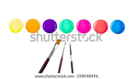 Paintbrushes and paint of various colors into containers . - stock photo