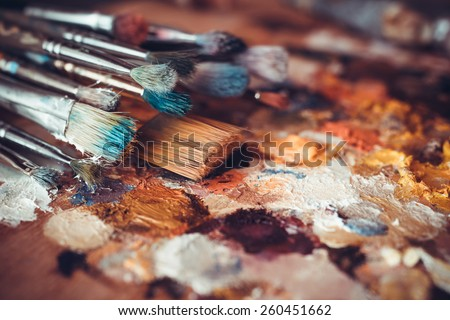 Paintbrushes closeup, artist palette and multicolor paint stains - stock photo