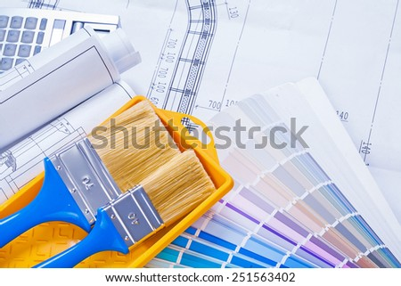 paintbrushes in paint can on color paleteed and rolled blueprints horizontal version  - stock photo