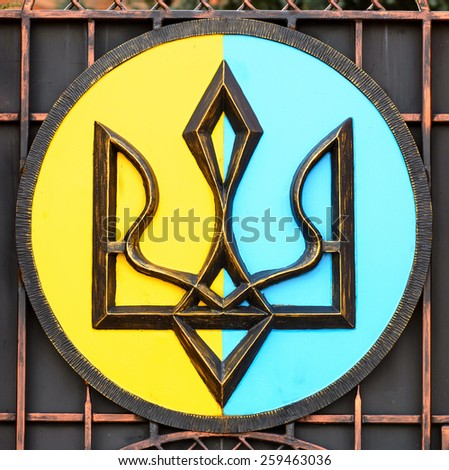Painted Coat of arms of Ukraine is on a black iron. National Emblem of Ukraine Painted Iron. Close-up - stock photo