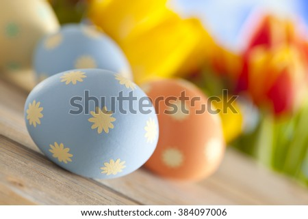 Painted Easter eggs and colorful spring flowers on sky background - stock photo