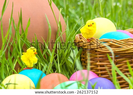 Painted Easter eggs and toy chickens on the background of a clay pitcher, wicker basket and green spring grass close up - stock photo