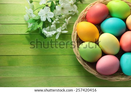 Painted Easter eggs basket and blossoming cherry tree flowers on wooden background - stock photo