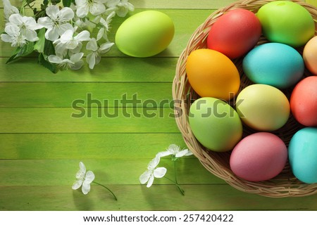 Painted Easter eggs basket and cherry blossom flowers - stock photo