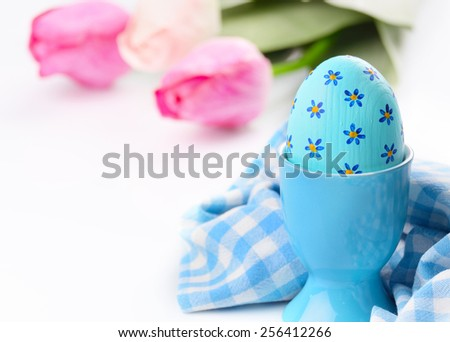 Painted easter eggs on white table in eggcup - stock photo