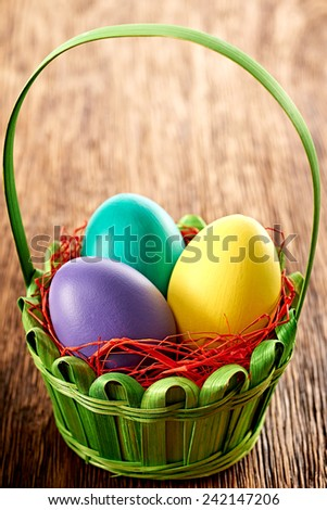 Painted Easter Eggs pink in decorated green basket with straw on wooden background - stock photo