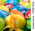 Painted easter eggs with bows over green background - stock photo