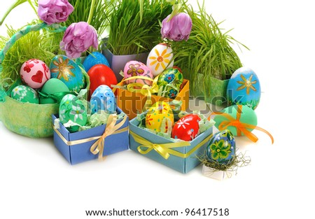 painted easter eggs with grass and tulips  on white background - stock photo