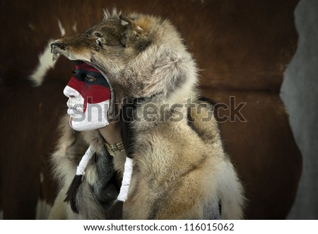Painted face, native american woman with war mask and wolf skin. Cracked paint. Young shaman girl with deer skull staff part of large series of painted tribal portraits - stock photo