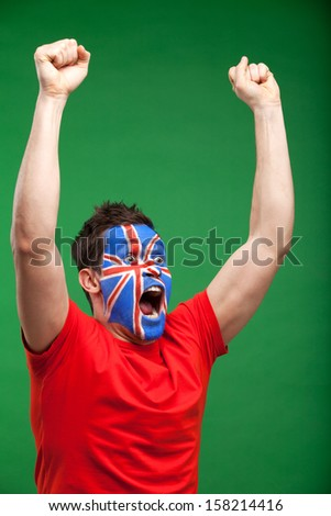 Painted football fan. man rooting for his team, raising his hands up - stock photo