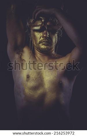 painted golden bodypaint, man with gold helmet, ancient warrior deity - stock photo