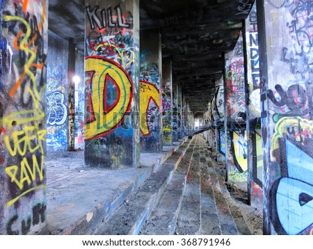 Painted graffiti posts inside abandoned industrial warehouse - landscape photo