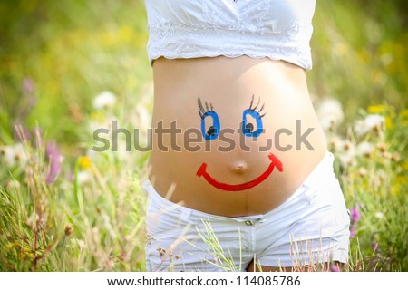 Painted  happy smiley face on the belly of pregnant woman - stock photo