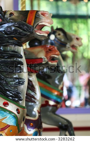 painted horses on a carousel ride at the fair - stock photo