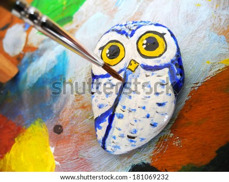 Painted stone owl on a palette - stock photo