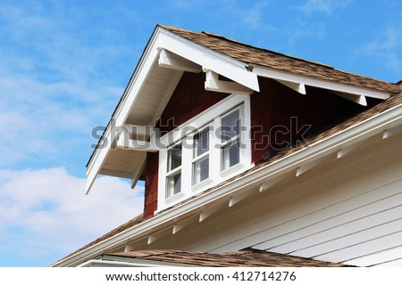 Painted wood corbels support the overhang on a gable on a residential structure. In architecture a corbel is designed to carry weight.