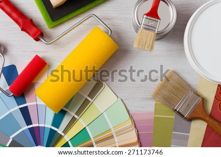 Painter and decorator work table with house project, color swatches, painting roller and paint brushes, top view - stock photo