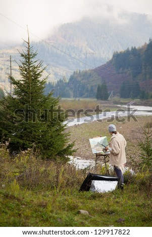 Painter at work in the mountains - stock photo