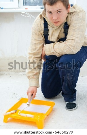 painter dipping paint roller - stock photo