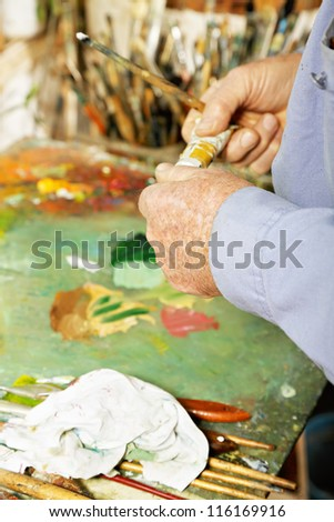 Painter hands with paint tube over palette - stock photo