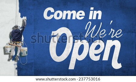 Painter hanging from building facade painting the words come in, we are open - stock photo