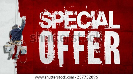 Painter hanging from harness painting a wall with the words Special Offer - stock photo
