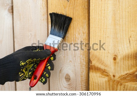 painter holding a brush and varnishes wooden structure - stock photo