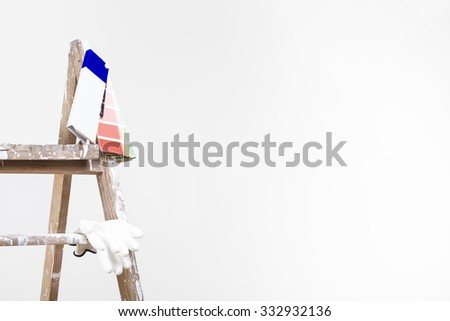 Painter man at work climbing a vintage wooden ladder and painting with paint roller - stock photo