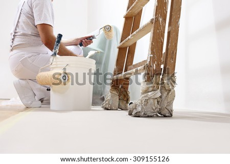 painter man at work with a roller, bucket and ladder, bottom view - stock photo