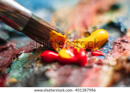 Painter mixes yellow and red oil paint on the palette. Closeup of paint mixing process in art workplace. - stock photo
