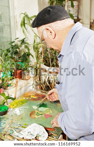 Painter mixing paints on palette sideview - stock photo
