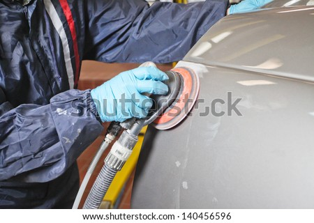Painter polishes a car body component - stock photo