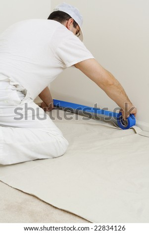 painter protecting the trim with blue masking tape - stock photo