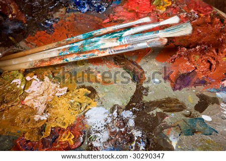 Painter's brushes and colorful almost abstract pallet full of paint - stock photo