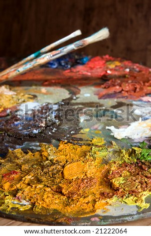 Painter's brushes and pallet full of paint - stock photo