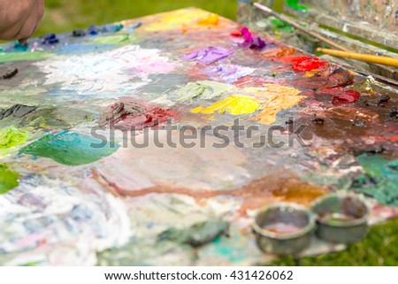 Painter's colorful bright palette with fresh blended oil paints and different paintbrushes in a park - stock photo