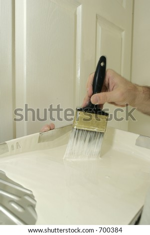 Painter's hands dipping a brush into white paint - stock photo