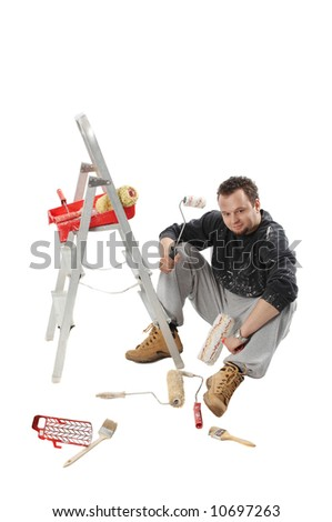 Painter sitting and holding a paint rollers - stock photo
