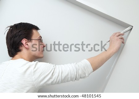Painter worker hand at decoration work painting a wall with brush