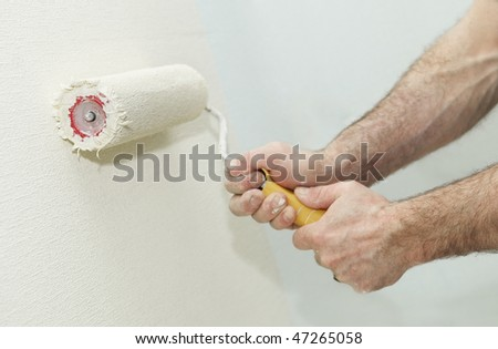 Painter worker hand at decoration work painting a wall with roller - stock photo