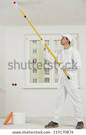 painter worker painting and priming ceiling with paint roller - stock photo