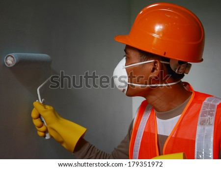 Painter worker wearing safety mask or safety work on job, painting of building house or apartment wall with roll - stock photo