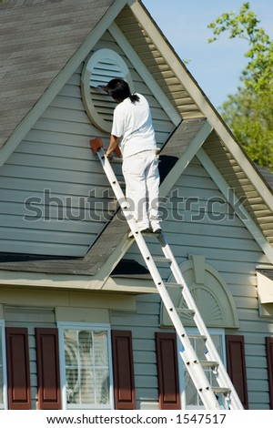 Painter working atop an extension ladder on a two-story suburban home.