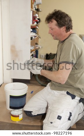 Painter working on remodeling wood inside a house