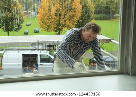Painter working outdoors on a window frame